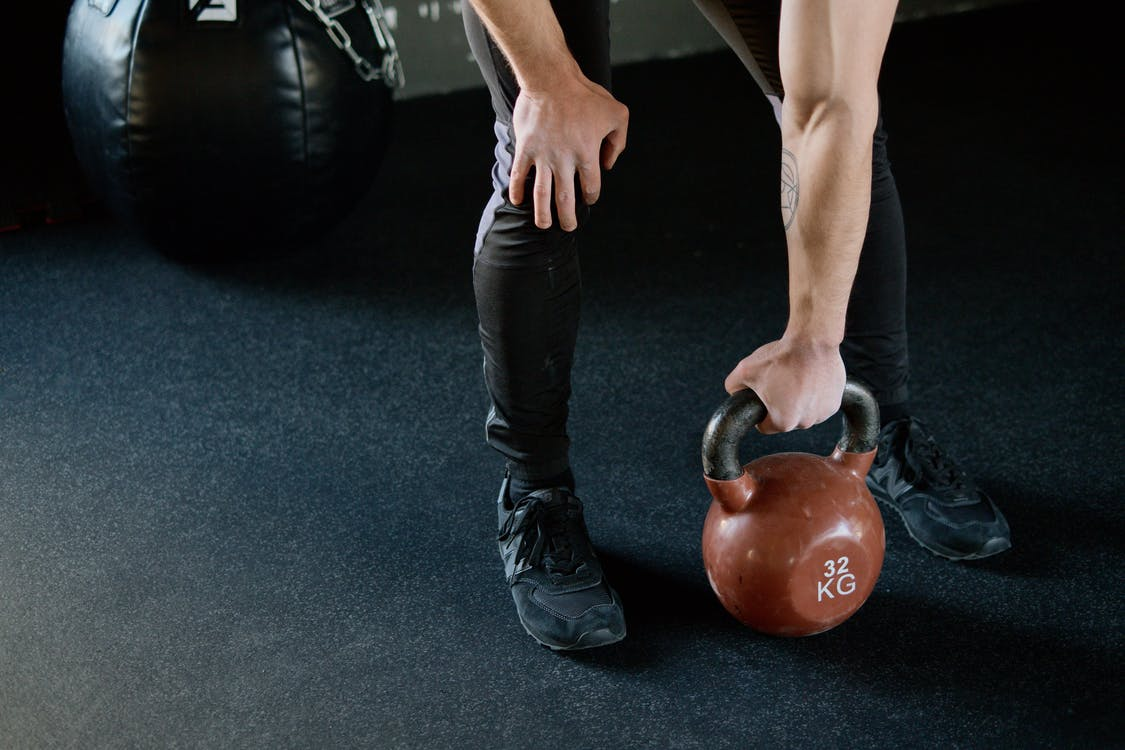Person Holding Red Kettle Bell