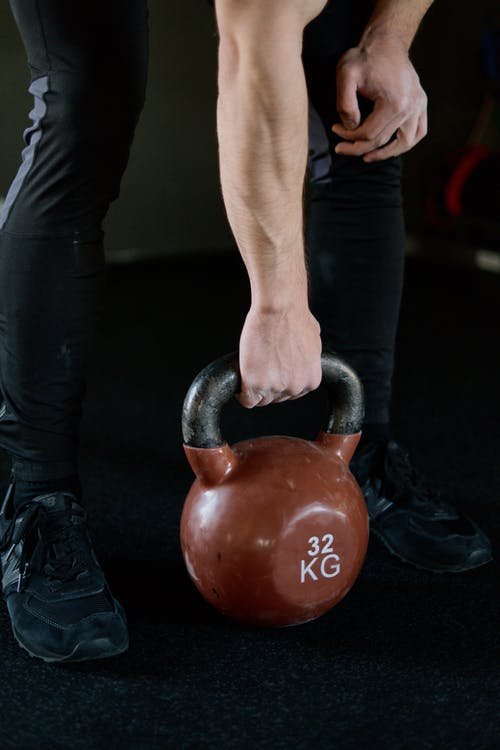 Person in Black Pants Holding Red Kettlebell
