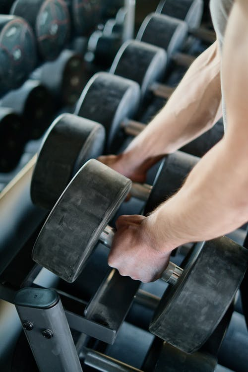 Person Taking Dumbbells from a Rack