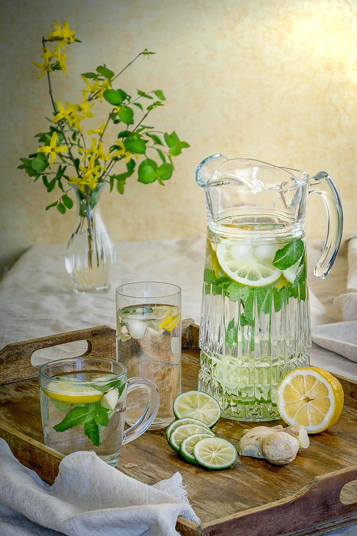 Lemon Juice in Pitcher Beside Glass Up and Sliced Lemons on Serving Tray