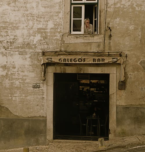 Facade of weathered building with window and door of bar