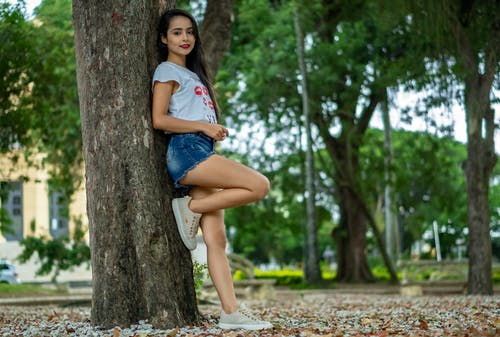 Positive girl in summer outfit standing near tree in park