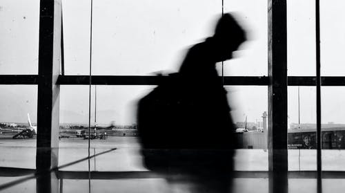 A Silhouette of a Person Walking in an Airport