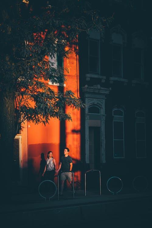 Couple walking on sidewalk of city