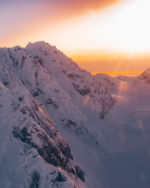 Snowy mountains under bright sunset sky