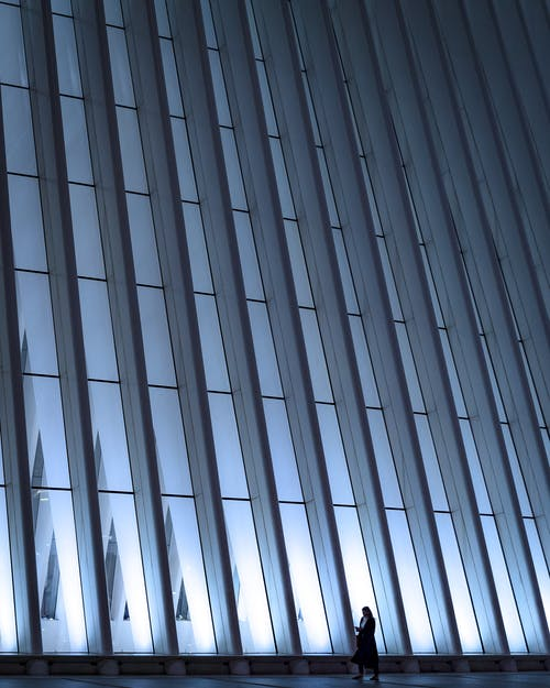 Woman walking along modern geometric wall of building