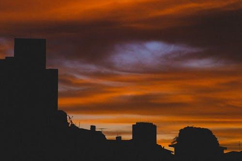 Dark city buildings under colorful cloudy sky at sundown