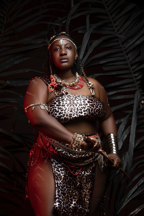 Dreamy chubby African woman in traditional wear in darkness