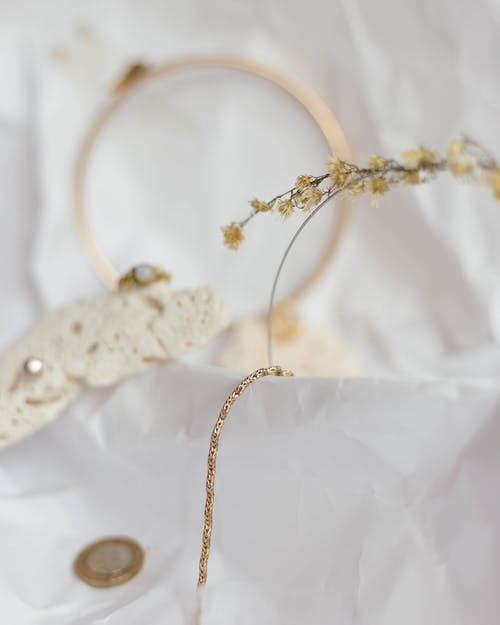 Gold and Silver Necklace on White Textile