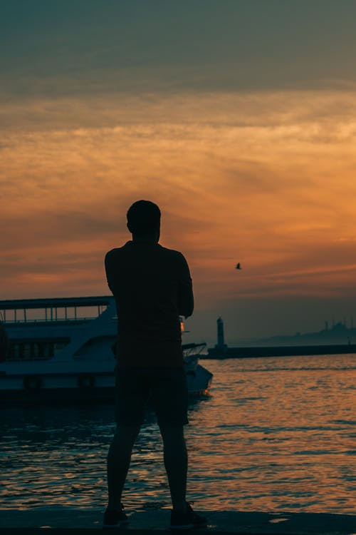 Back view of alone male tourist silhouette admiring rippled sea under colorful cloudy sky at sundown in twilight