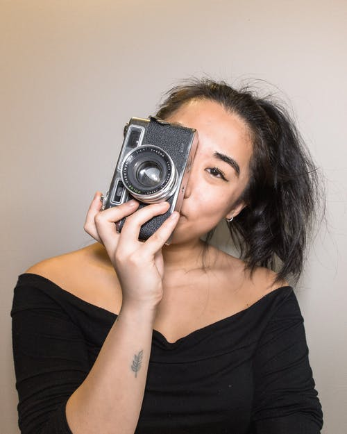 Woman in Black Tank Top Holding Black and Silver Camera