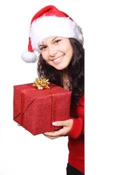 Woman in White and Red Santa Hat Holding Red Christmas Gift