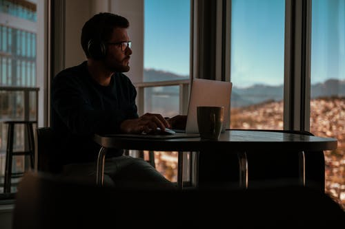Man in Black Jacket Wearing Black Sunglasses Sitting by the Table Using Macbook