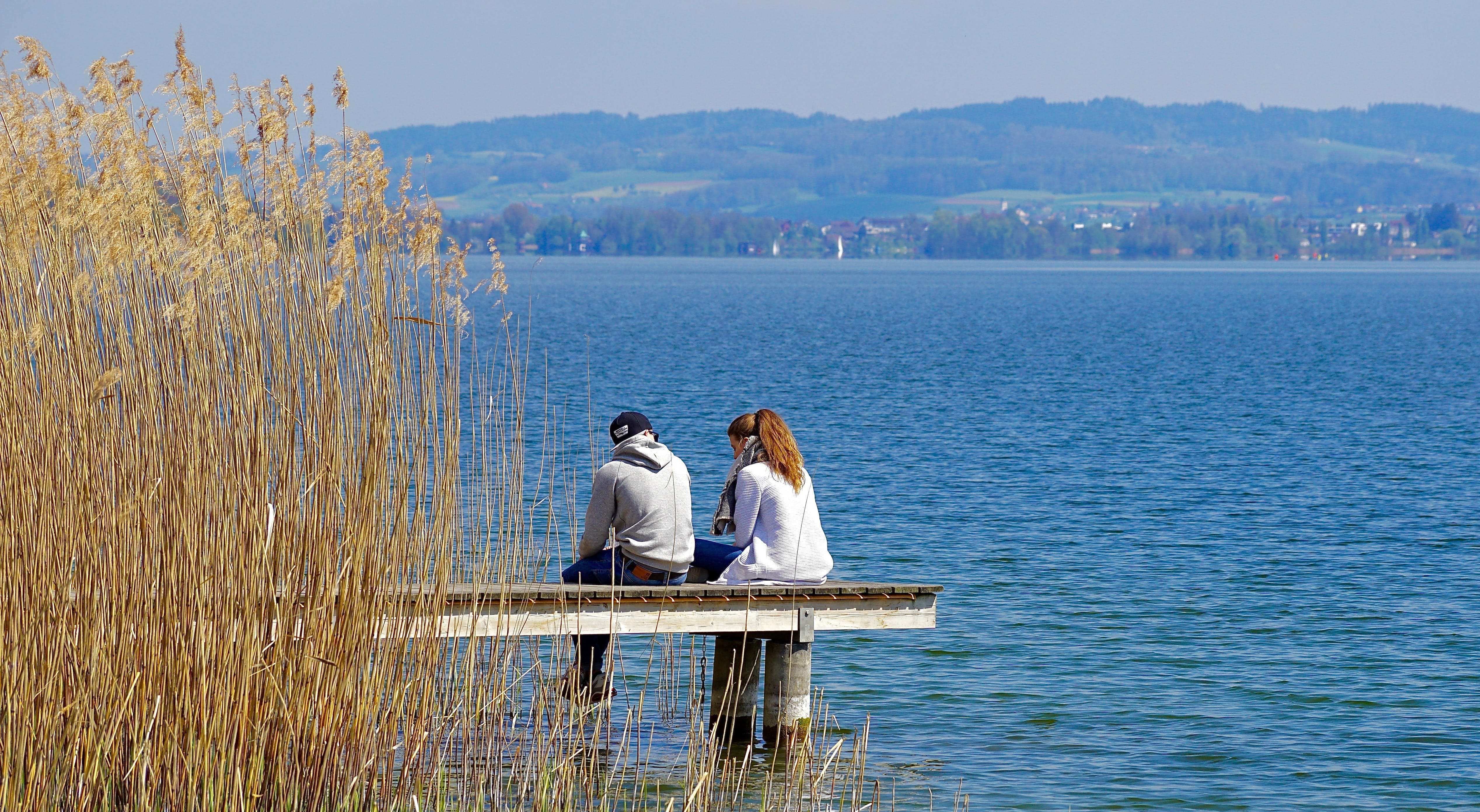 Man and Woman Sitting on Dock