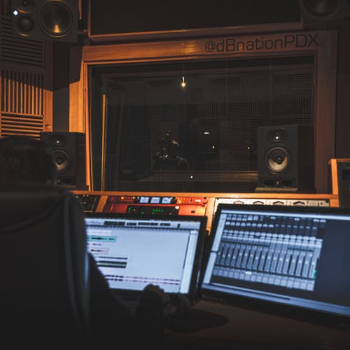 Unrecognizable sound engineer working with musical software on computer