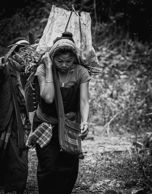 A Grayscale of a Woman Carrying a Tumpline