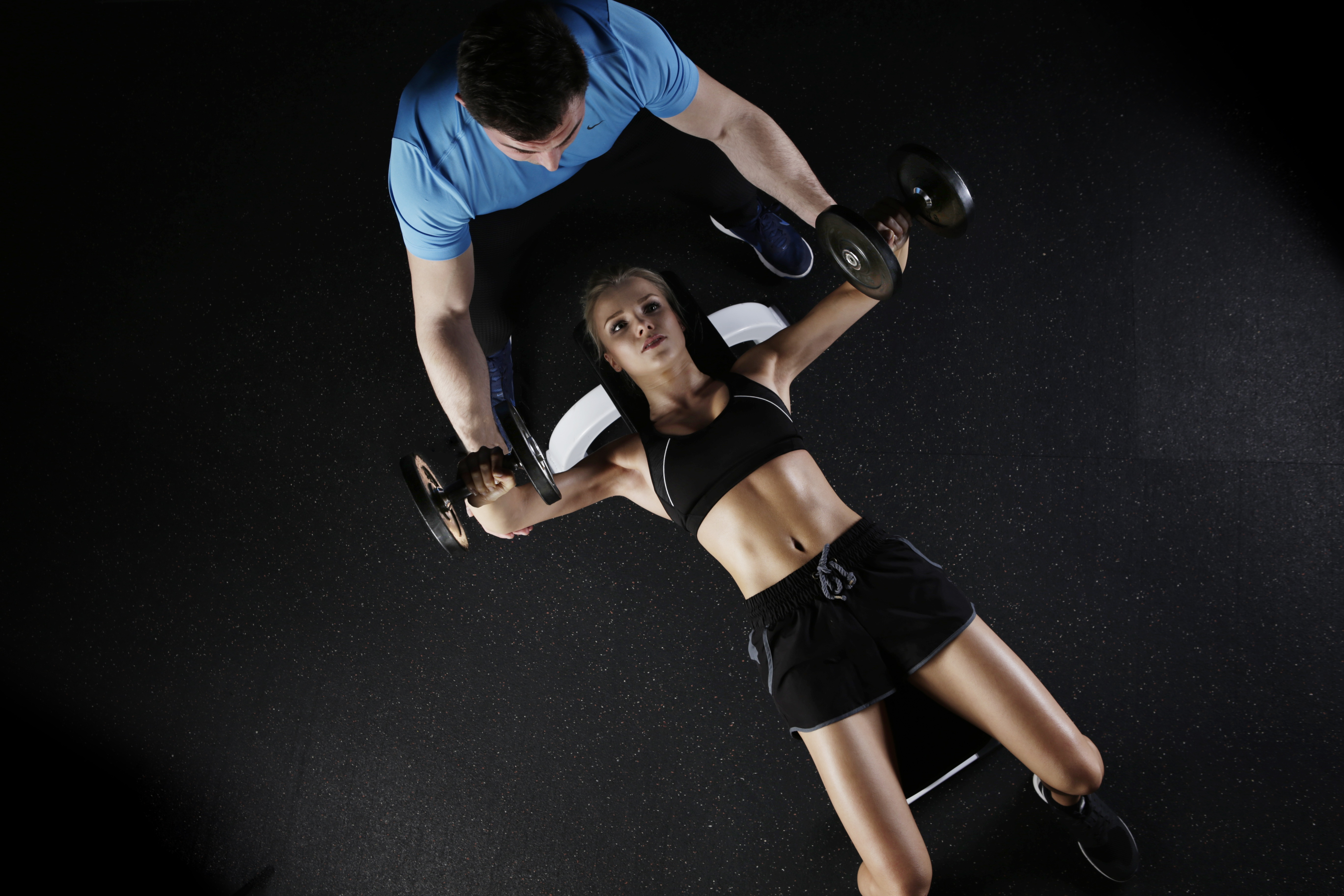 Woman Lying on Bench Press and Holding Barbell