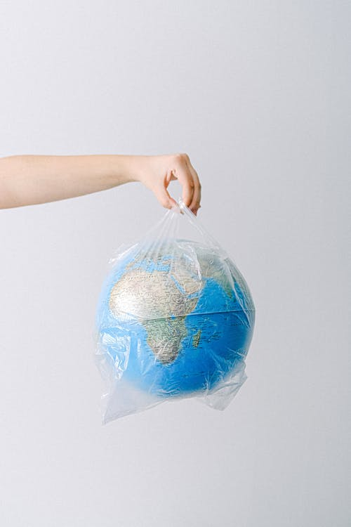 A Person Holding a Plastic Bag with a Globe