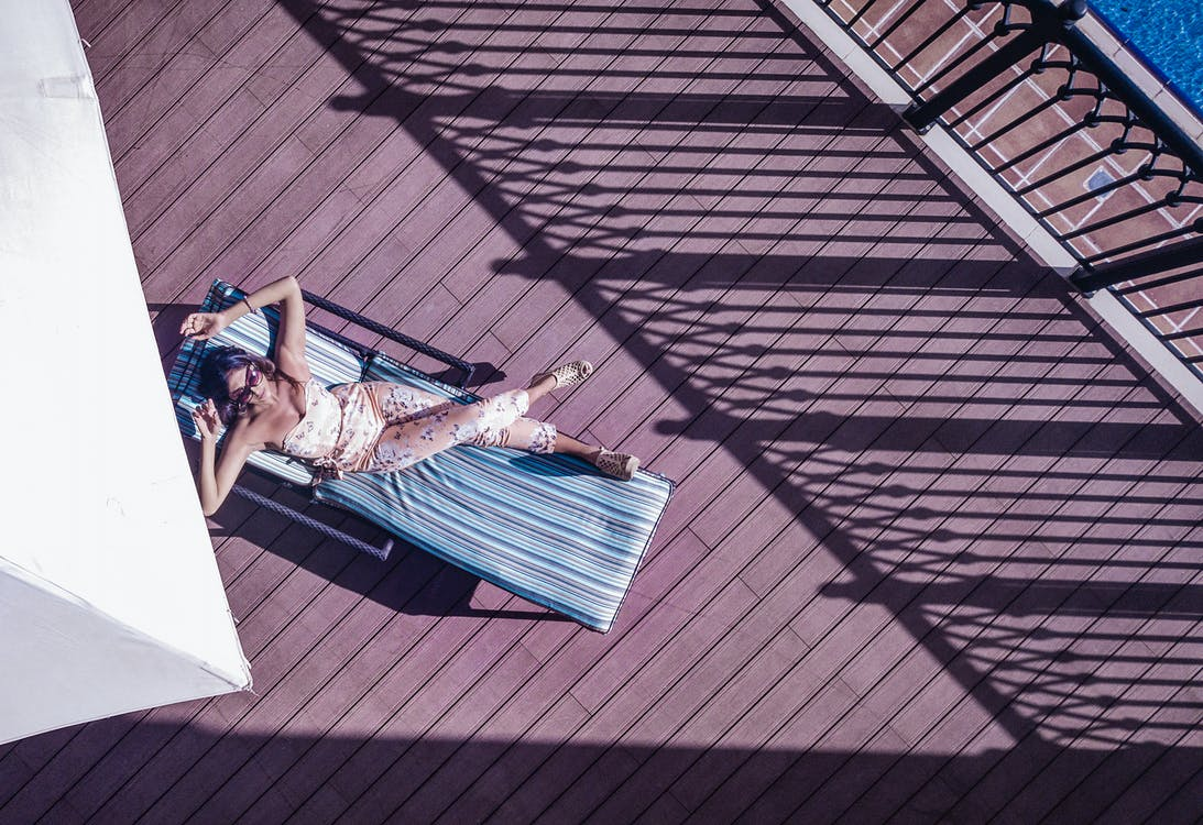 Top view of anonymous female traveler in sunglasses lying with crossed legs on sun bed on wooden floor near fence of hotel balcony in sunlight during trip