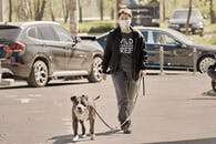 Woman in Face Mask Walking Dog