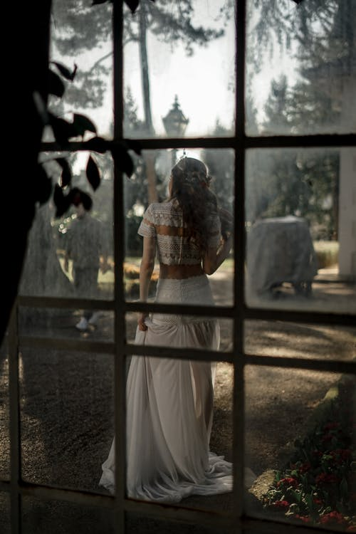 Elegant woman in wedding dress behind glass on pathway