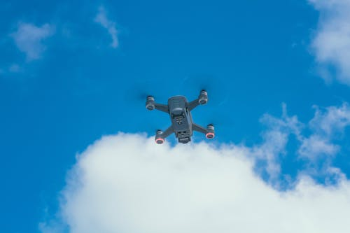 Blue and White Drone Flying Under Blue Sky