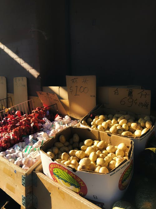 Assorted ripe vegetables placed in different boxes in stall in market in sunny day