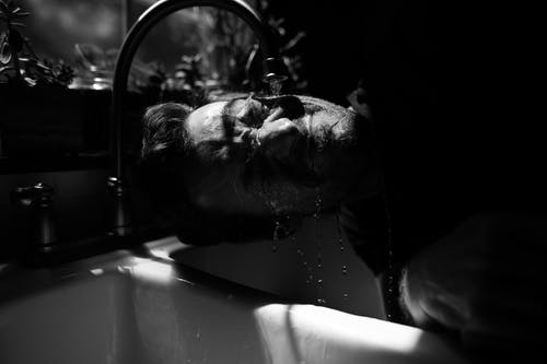 Black and white of bearded male with closed eyes standing near sink under water pouring from tap in sunny day