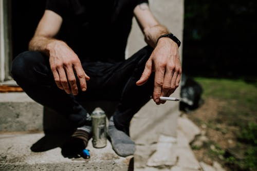 Crop man sitting on steps with cigarette in hand