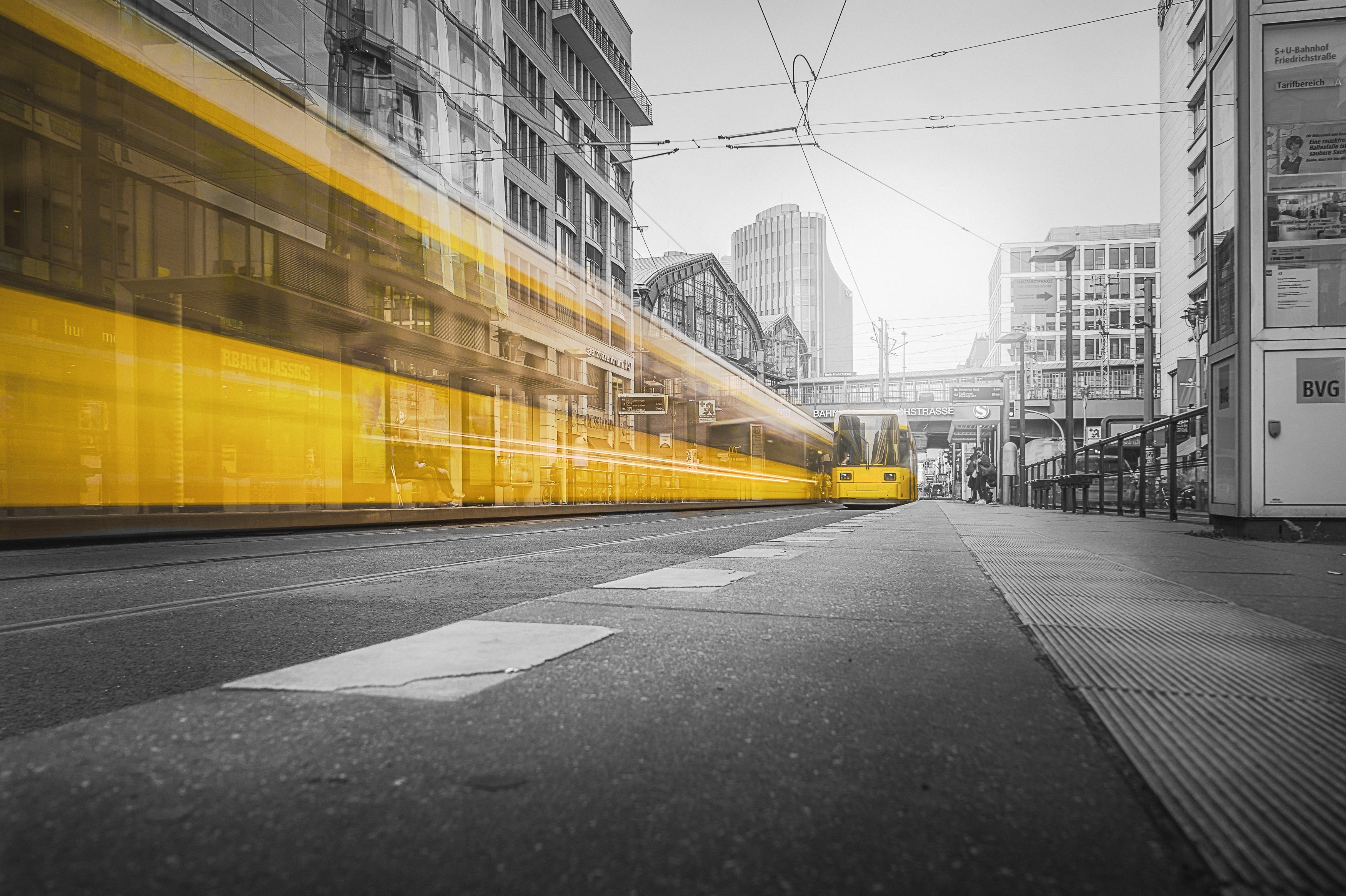 Selective Color Photography of Yellow Train Beside Building