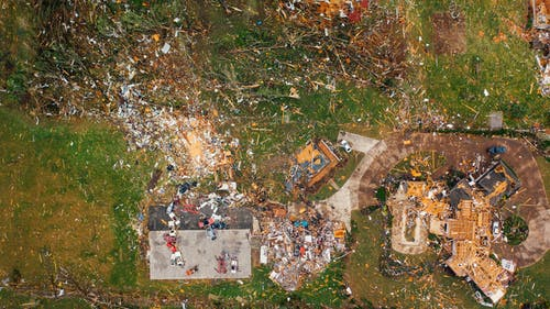 Aerial view of dramatic consequences of massive hurricane with ruined houses and kindling woods lying on green lawn
