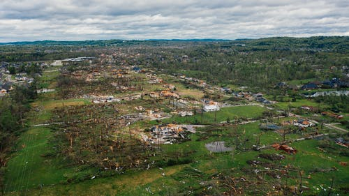Aerial view aftereffects of massive storm on small village including windthrown bent trees and destroyed buildings
