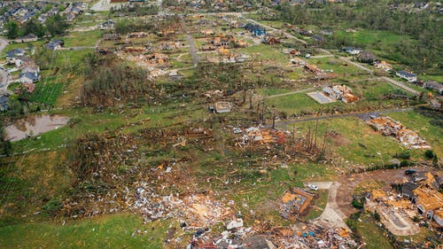 Destroyed village cottages and uprooted trees after tornado
