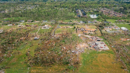 Drone view dramatic impact of massive hurricane on small village with destroyed cottages and uprooted trees