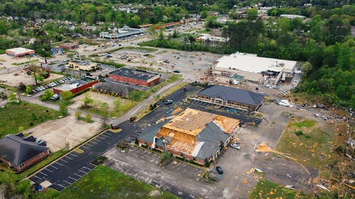 Aerial view of terrible consequences of thunderstorm on small town buildings with ruined roof and uprooted trees