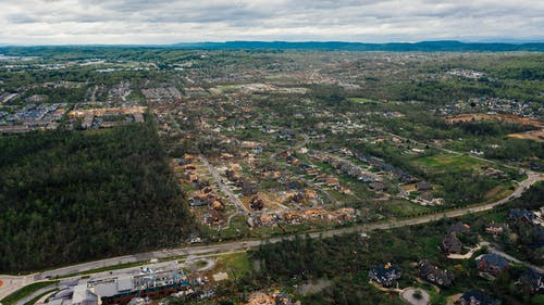 Aerial view of dramatic consequences of thunderstorm on town suburban district including damaged cottages and uprooted trees