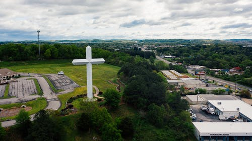 Drone view settlement with large white crucifix located on grassy lawn and surrounded with lush trees against commerce buildings