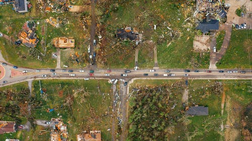 Aerial view of village houses ruined by wild storm near windthrown trees and electricity lines