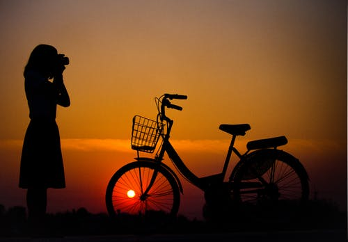 Silhouette of Woman Using Camera in Front of City Bicycle
