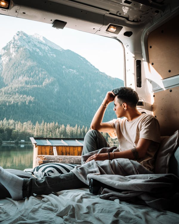 Man in White T-shirt Sitting on White Van
