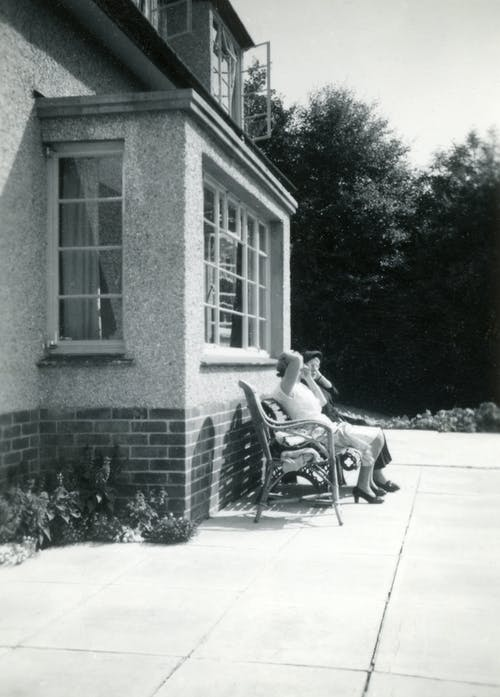 Grayscale Photo of People Sitting On A Bench Near Front Window Of A House