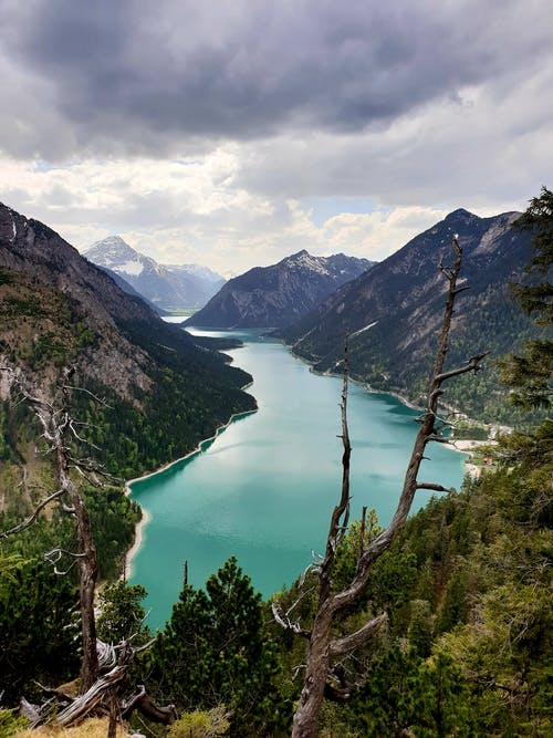 Breathtaking landscape of picturesque Lake Plansee surrounded by rocky mountains and lush foliage against cloudy sky in Tirol