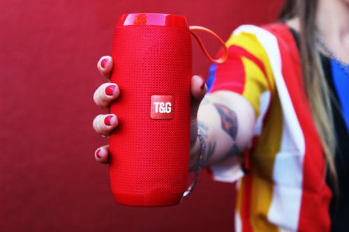 Unrecognizable woman demonstrating portable speaker against red background
