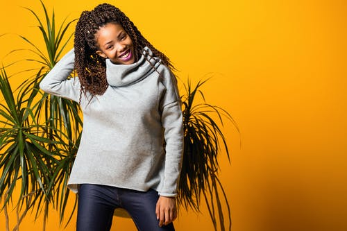 Cheerful young African American lady warm sweater touching long curly hair and smiling while standing near tropical plants against yellow background