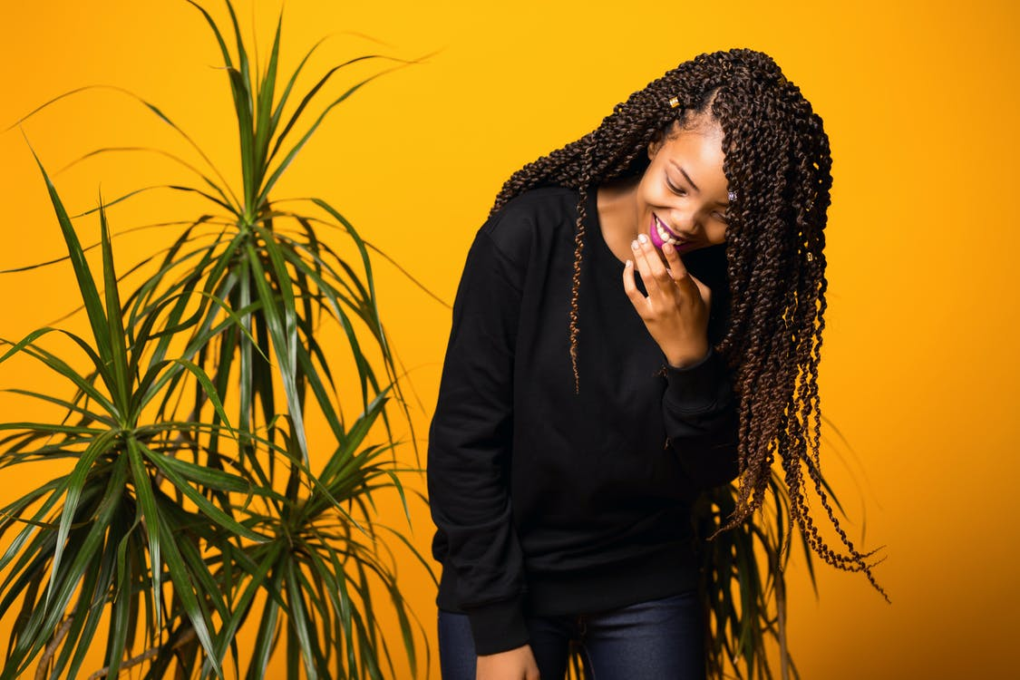 Cheerful young African American woman with Afro hairstyle touching lips while laughing against yellow background and looking down