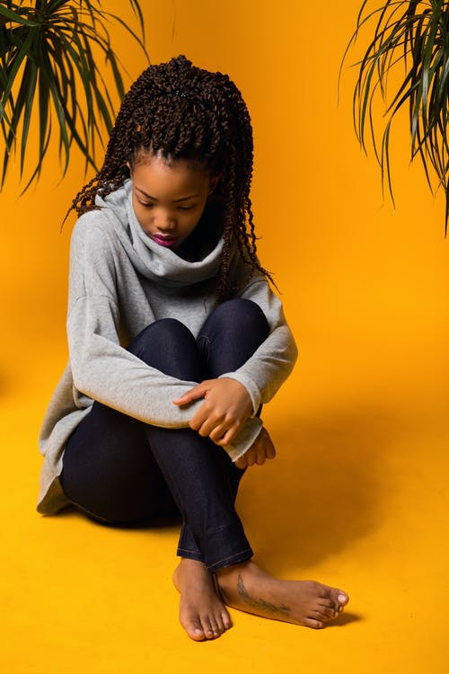 Upset young African American lady resting in yellow room