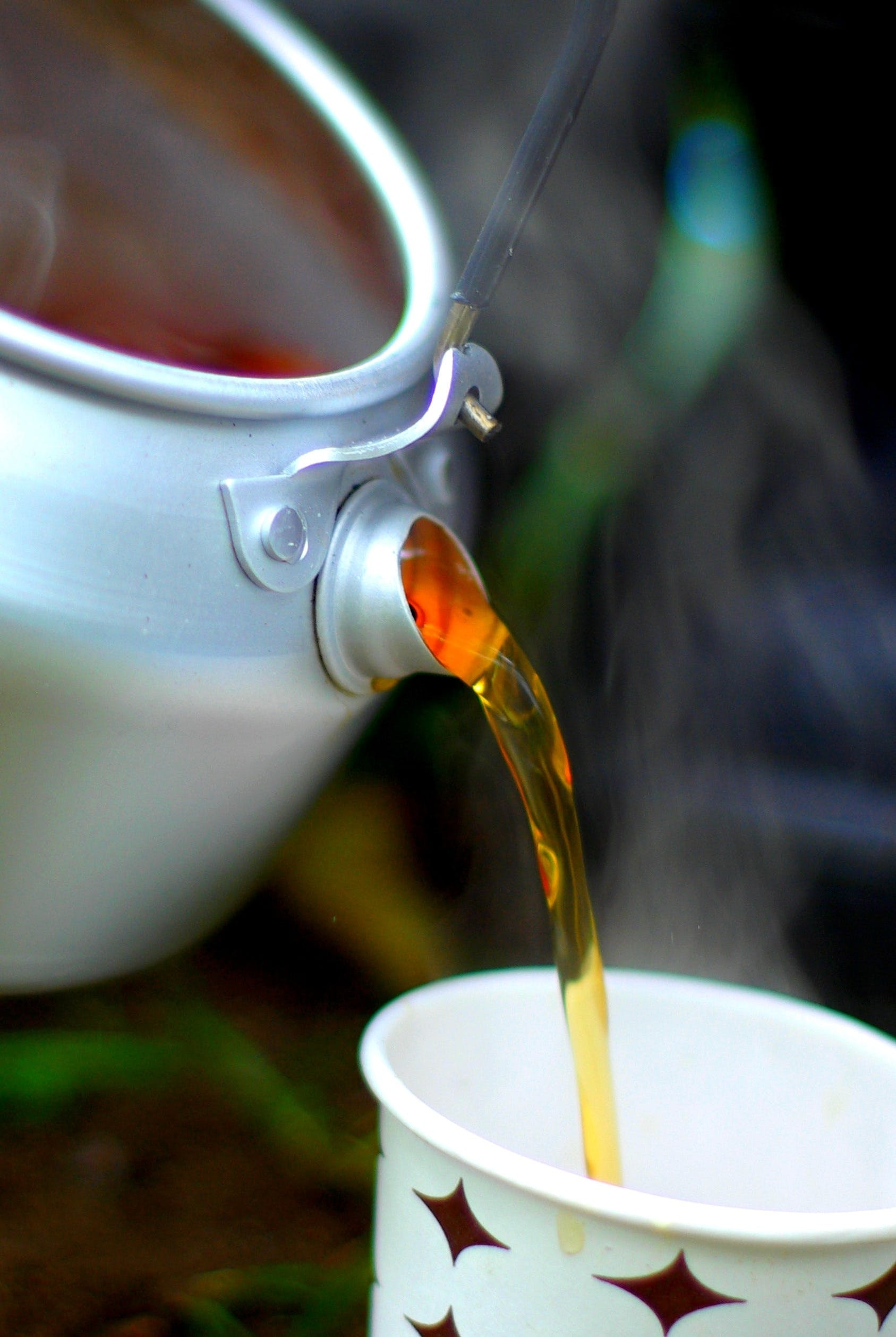 Selective Focus Photography of Teapot Pouring on White Mug