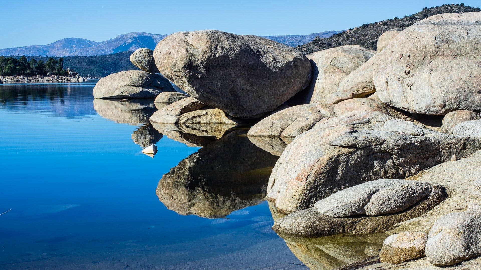 Gray Rock Formation Reflecting on Body of Water