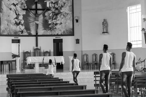 Grayscale Photo of People in White Shirts Walking on the Hall