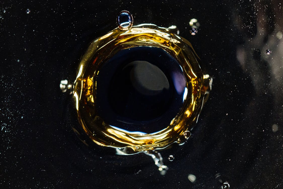 Closeup of droplet hitting surface of dark liquid and creating round shaped swirl and splashes as background